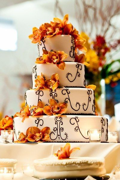Another beautiful wedding cake design. Love the orange and yellow flowers as well as the intricate scroll work
