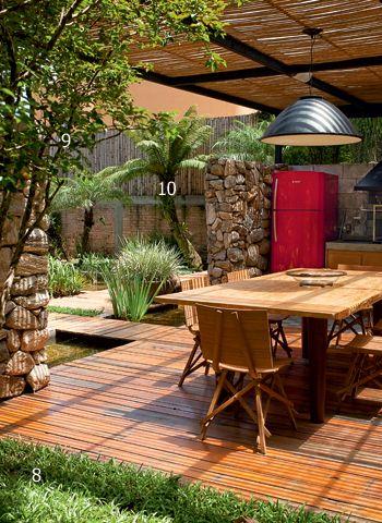 Na área gourmet, a pérgola tem cobertura de vidro temperado. Debaixo dele, réguas de bambu promovem um bonito sombreado na mesa assinada por Carlos Motta e no pendente da Reka Iluminação. Ao redor do deque, um tapete de grama-são-carlos (8) cerca a jabuticabeira (9). Ao fundo, o preservado xaxim (10), espécie em extinção, remanescente do paisagismo original da casa