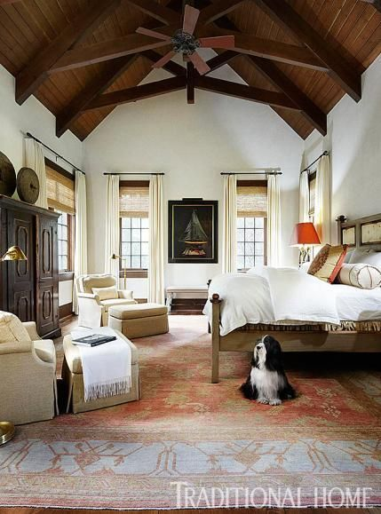 A muted palette prevails in the master bedroom. White walls contrast with the dark, vaulted ceiling.