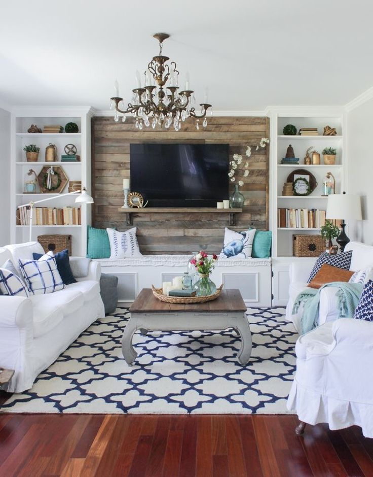 White Sofas Reclaimed Wood Accent Wall Built In Book Cases Blue And Pillows Rug A Crystal Lighting Fixture