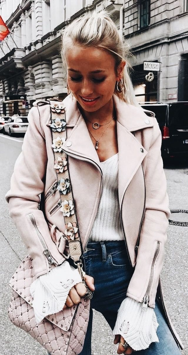 Pale pink leather jacket with white sweater and blue jeans.