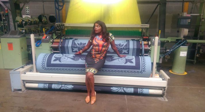 Ms Khulu Roberts next to a stunning blanket inside the Sesli Factory