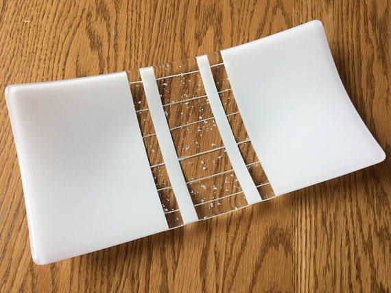 This beautiful fused glass tray was made with white art glass accented with center strips of white and clear art glass. An elegant centerpiece, its perfect for serving appetizers, cheeses, deli meats, or an assortment of hors doeuvres. This art glass serving platter measures 12 inches by 6 inches and rises 1.5 inches at the corners. Not intended for microwave use. Hand wash only. Designed and handmade in my home studio. Thank you for taking the time to visit my shop! For more handmade…