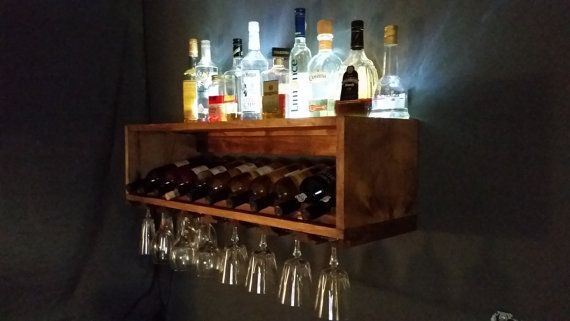 This mini bar shelf holds up to 10 standard sized (up to 12 inches) wine bottles neck down as they are meant to be stored. It will also hold up to 24 standard sized wine glasses. Keep your other alcohol stored along the back where it will be lit up by an LED strip hidden in the top of the shelf. Easily, and securely mounted by a wood cleat with 2 screws into the studs of your wall. Approximate size is 36 inches long, 9 inches tall, 11 1/4 inches deep. Listing for shelf only, glasses, alc...