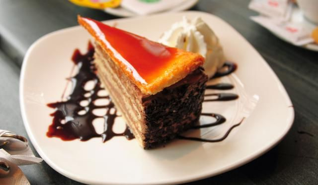 This authentic Hungarian Dobosh Torte recipe features seven layers of sponge cake filled with chocolate buttercream and topped with a caramel layer.