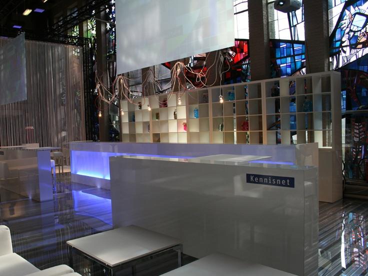 Campagneperiode 2010 Medium Live communicatie Een witte en steriele vormgeving gaven de stand een uitstraling van een laboratorium; waar –als in het onderwijs- zaken worden onderzocht, ontdekt en verbeterd. Het gebruik van kabels in de ruimte symboliseerde de netwerkfunctie. Een bestaande glas-in-loodwand werd geïntegreerd in het stand-concept en kreeg een centrale positie. Met riante zitbanken, transparante tafels, truss-systeem met beamers en transparante schermen