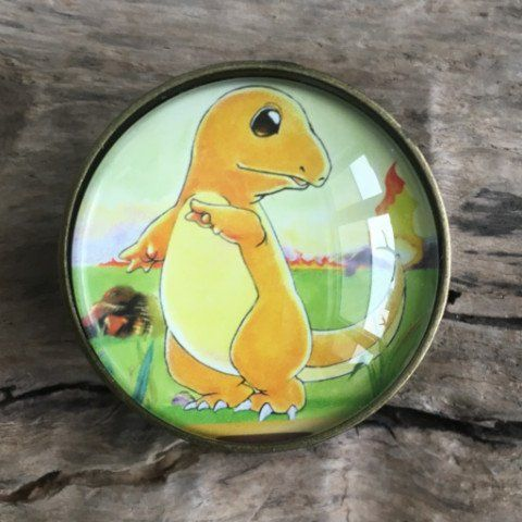 Pokemon Drawer Knobs - Cabinet Knobs - furniture knobs Charmander These drawer knobs are made with genuine images from original Pokemon Cards (Evolution). They are not copies or reprints. The image is placed behind a transparent glass orb and creates a fun addition to any drawer or cabinet.