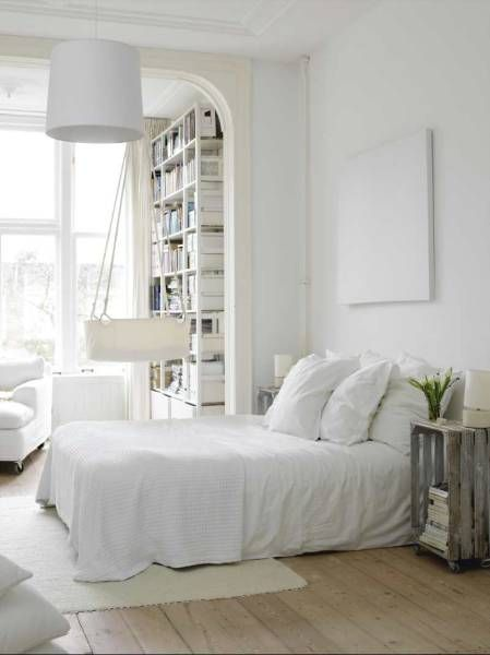 There is a white everything: low bed with big fluffy pillows, lamp, bookshelf with books, art as a headboard, a comfortable sit and there is also space for a hanging baby bassinet. The only color came from green stems, with white flowers, and an old crate as a nightstand, c.a.p.