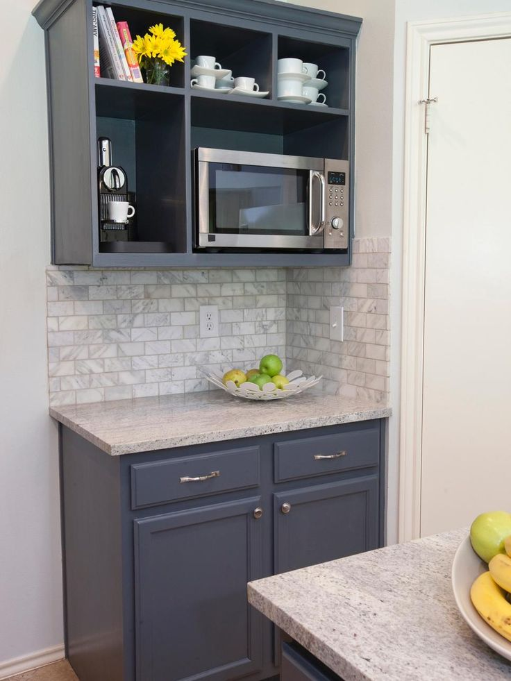 A mix of traditional cabinetry and open shelving provides maximum storage space in this kitchen featured on HGTV's Buying and Selling. The upper shelving unit frees up valuable counter space by housing the microwave and espresso machine, while a neutral subway tile backsplash complements the stone countertops.
