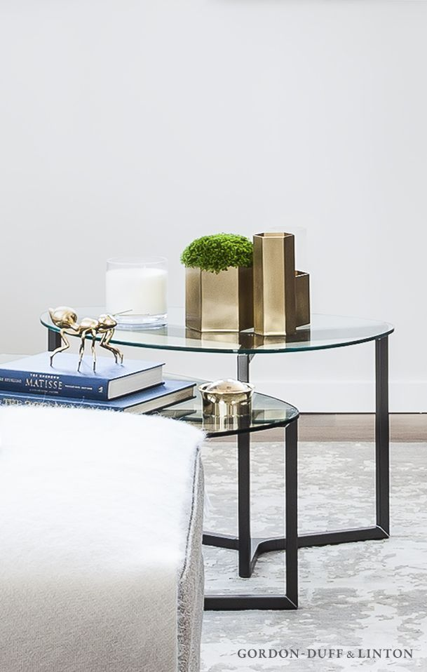 Living room detail of glass coffee tables with brass hexagonal vases, brass ant and brass magnifying glass.