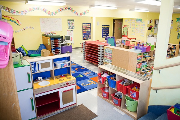 * This preschool room is dap. It is sectioned into learning areas. The yellow paint is warm and safe. The stairs have rails for multiple heights of children. The walkways are wide and the room is labeled and organized. - breeann l