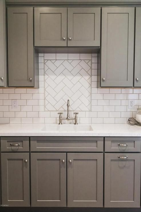 white and gray kitchen features gray shaker cabinets paired with white quartz countertops and a white - White Kitchen With Subway Tile Backsplas