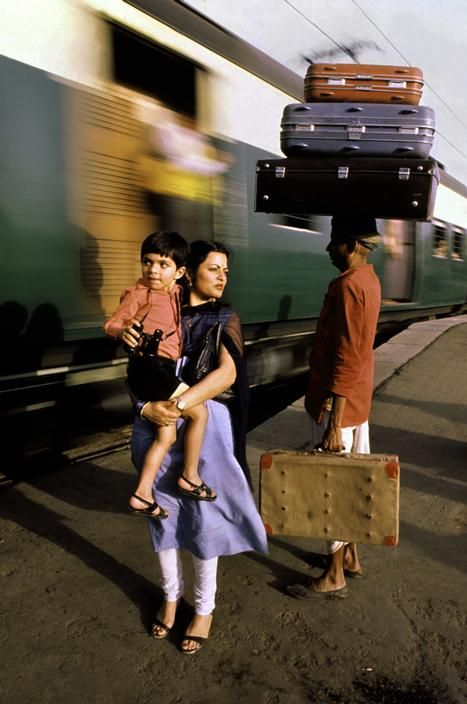 Steve McCurry  INDIA. New Delhi. 1983. Train porters with red jackets and brass tags at a New Delhi railway station. They charge 20 cents per bag.  Magnum Photos