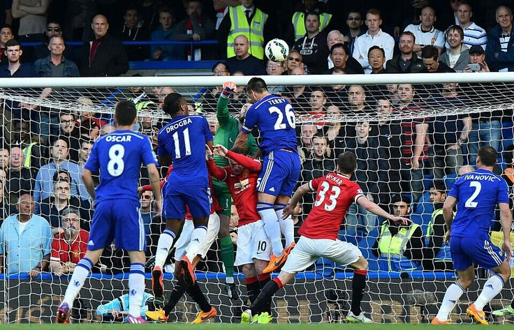 18 April 2015: Manchester United goalkeeper David De Gea bravely punches a Chelsea cross clear under pressure from Didier Drogba and Blues' skipper John Terry...