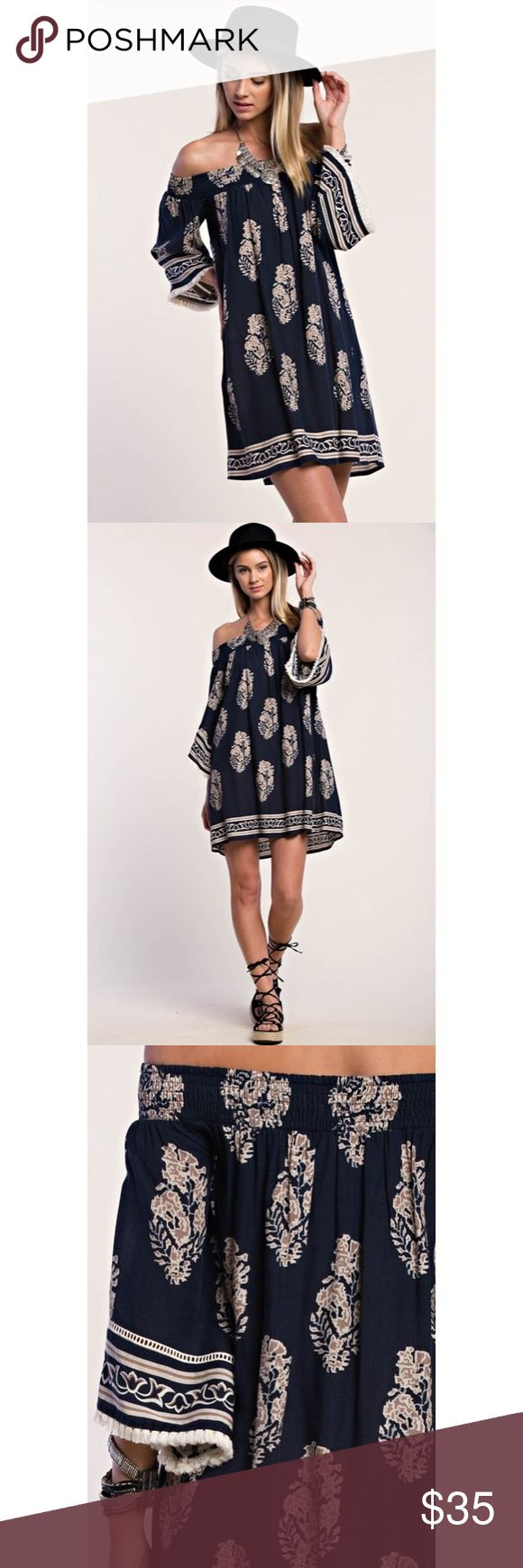 """RESTOCKED!!! Boho Navy Off Shoulder Dress Boho Beauty Off-Shoulder Dress  Navy with floral/leaf pattern Off shoulder loose fitting silhouette Bell sleeves with cream colored tassels 100% Rayon Length is approx 29"""" (measured flat) Flattering for many body types Perfect for festival season!  Price firm unless bundled Top rated seller Fast shipping No trades Boutique Dresses"""