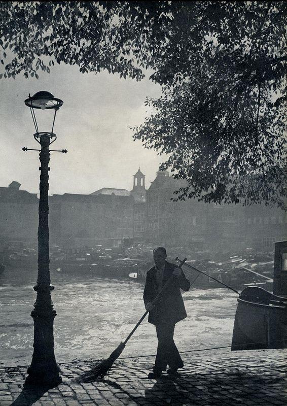 1957. Man sweeps the street at the Oude Schans in Amsterdam. Photo Kees Scherer. #amsterdam #1957 #oudeschans