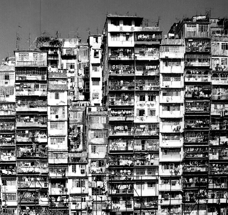 Kowloon Walled City in Hong Kong, residing 33,000 people in area of 0.3km2. This is not one building, but individual blocks built with no planning permission. Note how the windows dont line up.