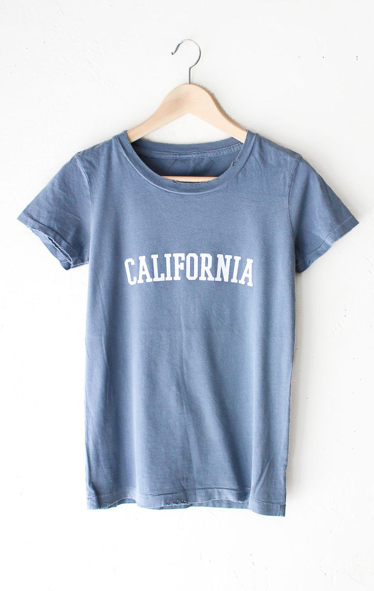 """- Description Details: 'California' relaxed fit destroyed tee in vintage blue with unfinished hem & grinding on neck and bottom hem. Brand: NYCT Clothing Measurements: (Size Guide) S: 34"""" bust, 24.5"""""""