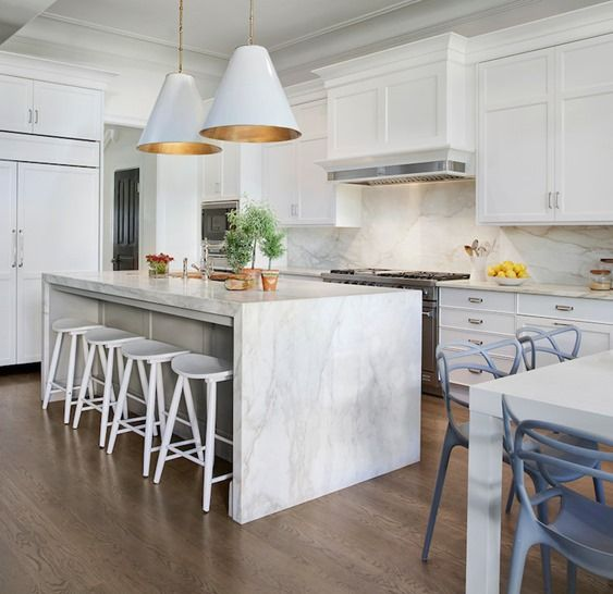 gorgeous combo of traditional and contemporary styles in this beautiful white kitchen -- particularly love the marble waterfall island countertop and blue chairs
