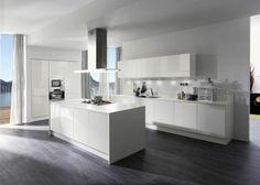 Die moderne Küche mit Kochinsel besteht aus elegantem Hochglanz in Weiß