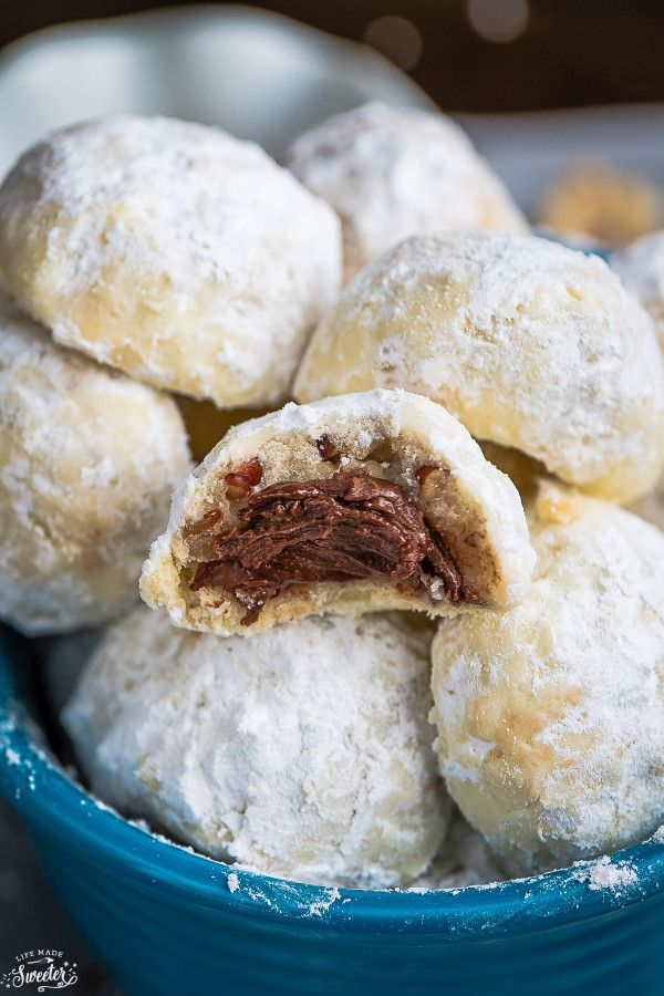 Nutella Stuffed Snowball Cookies are perfect for your Christmas cookie tray! Classic buttery shortbread-like cookies that are so easy to make with a surprise Nutella filling inside!