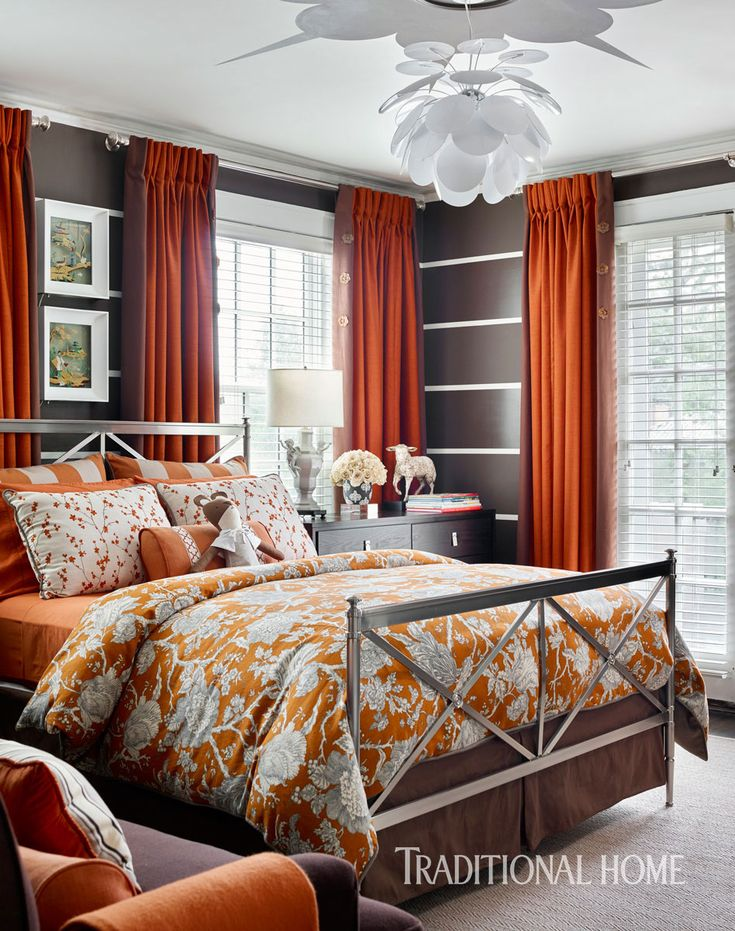 n daughter Vera's room, bright orange provides a cheerful contrast to deep brown walls. Floral motifs appear on the bedspread, drapery hardware, and even the playful light fixture overhead.