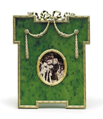 A SILVER-GILT MOUNTED NEPHRITE PHOTOGRAPH FRAME MARKED FABERGÉ, WITH THE WORKMASTER'S MARK OF MICHAEL PERCHIN, ST. PETERSBURG, 1899-1903; sold 22,500 USD; CHRISTIES 6/22/16.