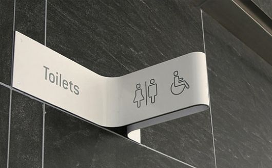 Crafted signage - Guess specification - (5mm acrylic thermal formed shape, spray painted, text and graphic etched and infilled to match black)