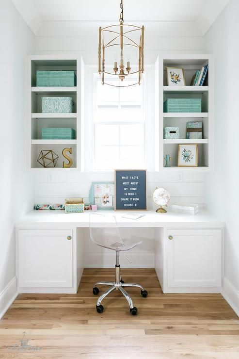 White styled shelves accented with Tiffany blue accents flank an uncovered window and are mounted to a white shiplap backsplash above a built in white office desk fitted with white cabinets adorning gold knobs and seating an acrylic task chair lit by a gold lantern.