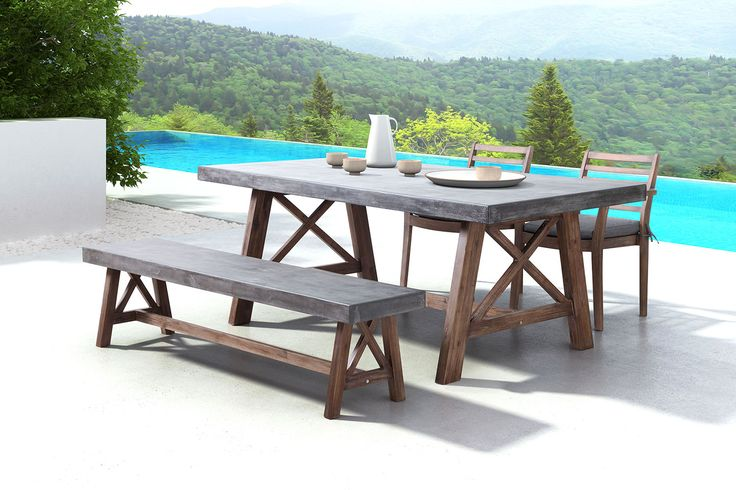 Farm-style Dining. Dinner on your patio will never be the same with the Santo outdoor farmhouse dining table. With a wood base that draws inspiration from charming barn trestles and is made from solid acacia wood, this table features an alluring and contemporary dark walnut finish. Its beautifully contrasting top is constructed with a non-porous epoxy and cement mix that is designed for easy cleaning with household detergent. Customer assembly required.   A web-exclusive product. Item is not…