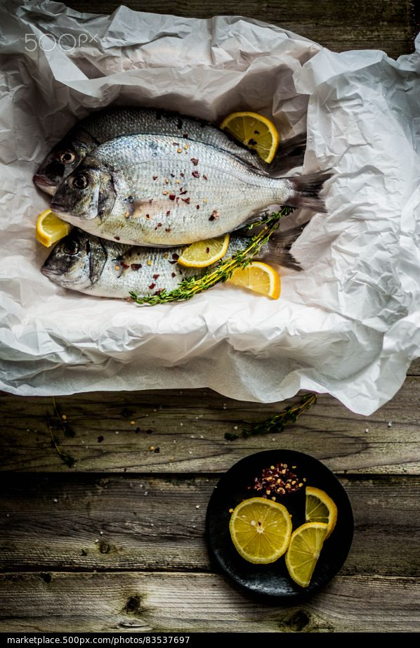 Fresh sea bream on wooden board - stock photo