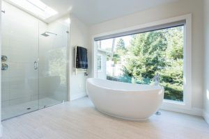 This contemporary bathroom has a freestanding tub, enclosed glass panel shower and huge wall sized window. / Photo by JMJ Studios