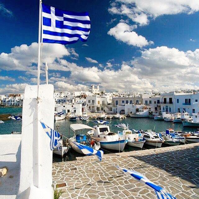 Stunning Naoussa village , at Paros island (Πάρος) ☀️. The amazing white & blue of Cyclades and the Greek flag waving ! Simple and beautiful .