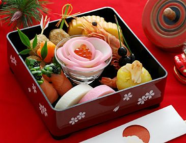 "Japanese food ""Osechi"". Kamaboko flower in center with either pomegranate seeds or maybe caviar."