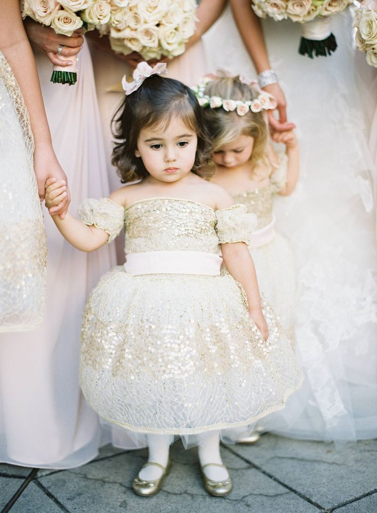 Flower girls wore beautiful white dresses embellished with gold sequins to match their ballet flats. #flowergirls Photography: Jose Villa Photography. Read More: http://www.insideweddings.com/weddings/destination-beverly-hills-wedding-with-celebrity-chef-performers/467/