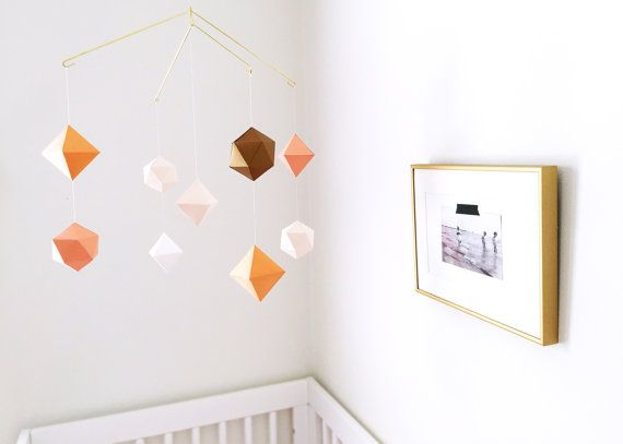 Deze heldere + geometrische mobiele is het perfecte accessoire om weer te geven boven je wieg. Er zijn 9 vormen in deze mobiele en de kleuren omvatten blozen, tangerine, koraal, wit en goud. Deze mobiele ook beschikt over een mooi gepolijst gouden frame en wordt geleverd met een haak die gemakkelijk in uw plafond waardoor het zeer gemakkelijk om op te hangen is geschroefd.  De shapes worden met de hand gemaakt met duurzaam karton.  Afmetingen van het hele mobiele als geheel: 15-inch diameter…