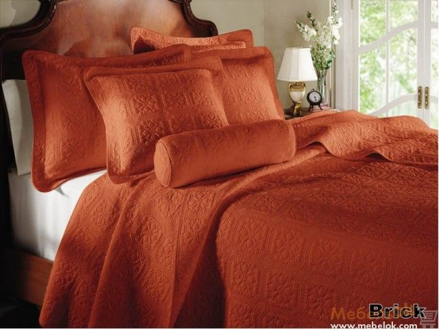 Покрывало и подушки кирпичного цвета для спальни в классическом стиле.