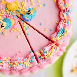 Perfectly Delightful Vanilla Birthday Cake filled & frosted with pink whipped vanilla frosting and topped with sprinkles. My go-to birthday cake recipe!
