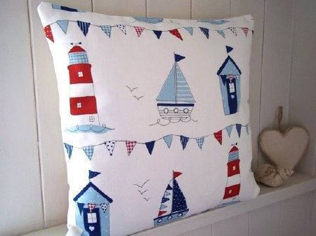 Fryetts -  Fryetts Fabric Collection - A blue, red and white scatter cushion printed with boats, lighthouses, bunting and beach huts, beside a wooden heart