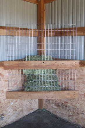 Super simple DIY hay slow feeder for stall. place at ground level. add grain pan top (with nubbins or holes to slow grain consumption. add opening in aisle wall at top back for filling. make big enough for half bale. add slant floor to gravity-drop hay to front for access.