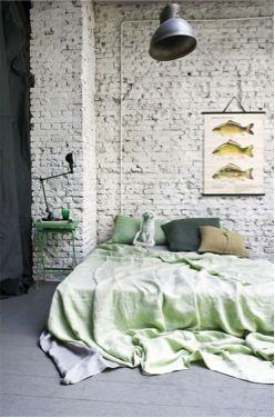 Witte bakstenen muur achter bed