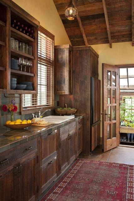 Kitchen -- brown wood, yellow walls, Adobe tiles.  Also note greenhouse attachment!