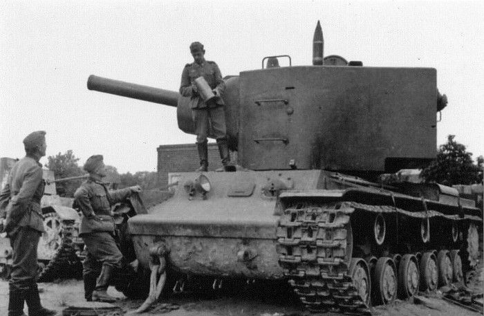 1941 German soldiers examine abandoned Soviet heavy tank KV-2.Perfect target. To the left you can see the light tank flamethrower HT-26 (Chemical T-26) – also abandoned.