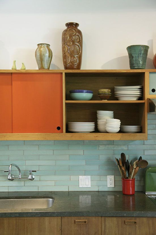 A vintage inspired kitchen.  The mint green back splash in contrast with the orange cabinetry is hip and cool.