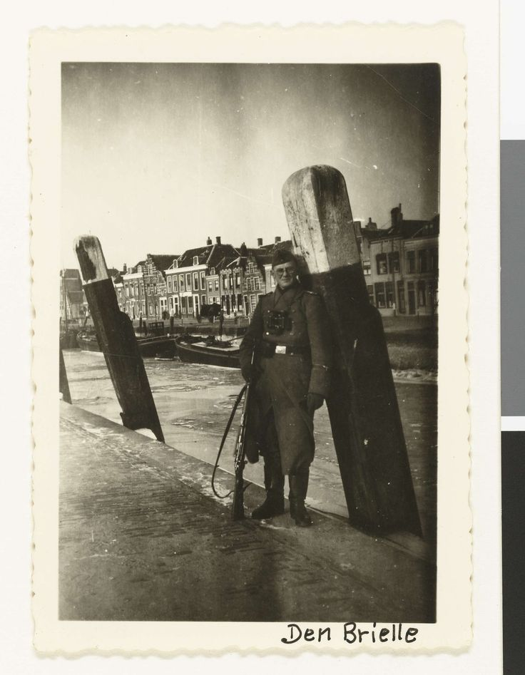 Anonymous | Een Wehrmacht soldaat in een haven, Anonymous, 1940 - 1941 | Een Wehrmacht soldaat heeft  zich laten fotograferen leunend tegen een aanmeerpaal in de haven van Brielle. (Zelfde soldaat als op NG-2007-5-35 t/m 38) De soldaat heeft een pet op, draagt een bril, een verrekijker en een geweer. Het is winter, er ligt ijs op het water.