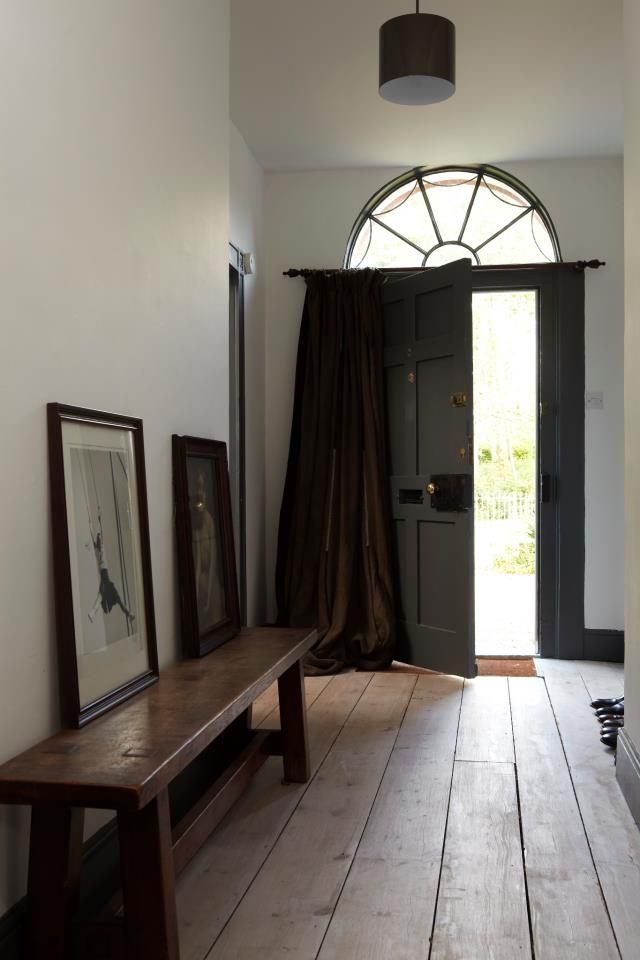 Rustic and Modern elements. Belgian oiled floorboards, curtain holds out the draft in an old house. Modern light fixture and bench for taking off boots.
