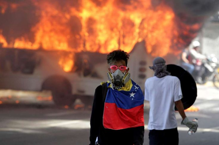 Demonstrators stand next to a bus burns near a protest against Venezuela's President Nicolas Maduro'... - REUTERS/Christian Veron