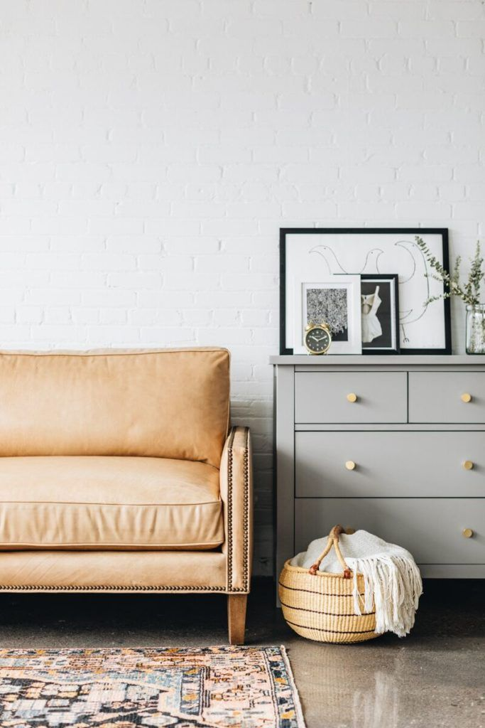 Light Leather Couch + Gray Dresser with Gold Knobs, Wicker Basket, Exposed White Brick Wall // Interior Design, Living Room Ideas