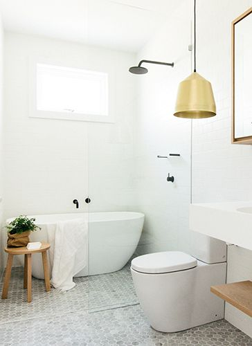 Bathroom: light grey marble hexagon mosaic floor tile, wall-faced toilet, freestanding bathtub in shower stall, frameless shower screen, black tapware, gold pendant light, wooden mirror cabinet and shelf under wall-mounted basin