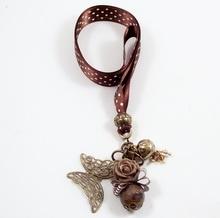 Cuelgamóvil bixut realizado con lazo, ágata, swarovski y piezas de metal de fantasía.